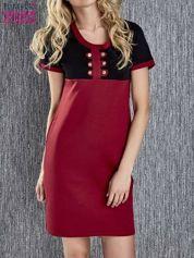 Czerwona sukienka ze złotymi guzikami