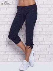 Granatowe spodnie capri z boczną kieszonką i dżetami