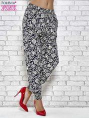 Granatowe zwiewne spodnie alladynki we wzór kwiatków