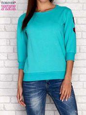 Zielona bluza z naszywkami na rękawie