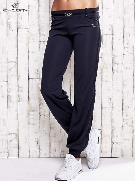 Granatowe spodnie dresowe z ozdobnym paskiem