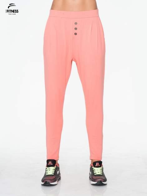 Jasnokoralowe spodnie dresowe typu baggy z guziczkami