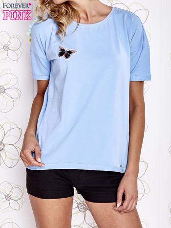 Jasnoniebieski t-shirt z naszywką motyla i pomponami