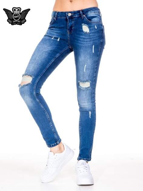 Niebieskie spodnie jeansowe rurki z dziurami i wytarciami