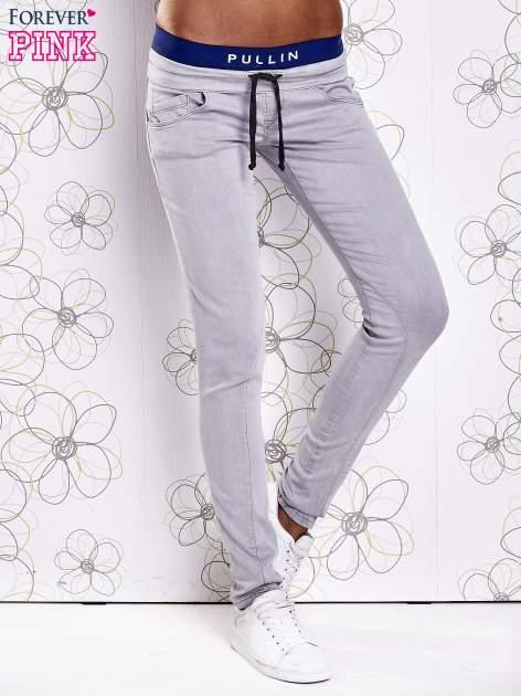 Szare spodnie z przeszyciami i ciemnoniebieską gumką w pasie