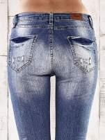 Ciemnoniebieskie spodnie jeansowe rurki z przetarciami i dziurami