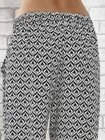 Czarne zwiewne spodnie alladynki we wzór geometryczny