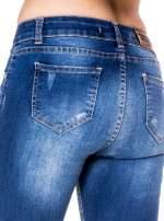 Niebieskie spodnie jeansowe rurki z rozjaśnianą nogawką i rozdarciami na kolanach