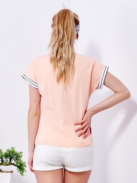 Brzoskwiniowy t-shirt z kieszonką i naszywką                                  zdj.                                  2