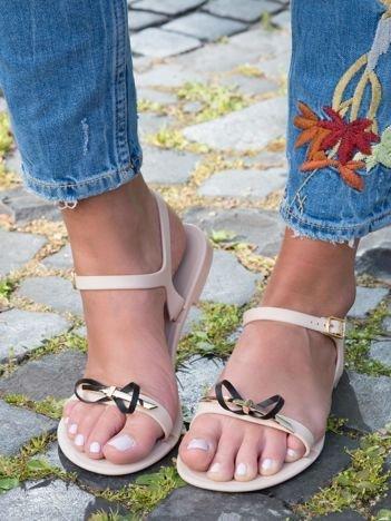 Beżowe sandały z ozdobną czarną kokardką i złotą blaszką na przodzie zapinane na sprzączkę
