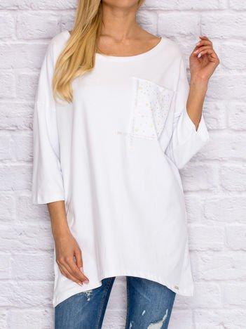 Biała bluzka z błyszczącą aplikacją na kieszeni