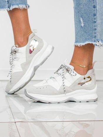 Białe buty sportowe z lustrzaną wstawką na boku cholewki