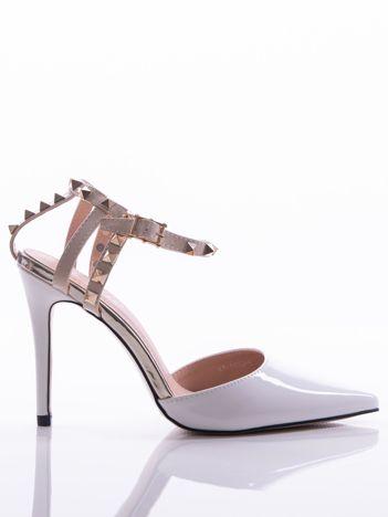 Białe lakierowane sandały na szpilkach z ozdobnymi paskami na tyle cholewki zdobione złotymi ćwiekami