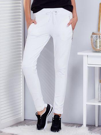 Białe spodnie dresowe z suwakami