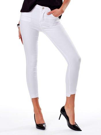 Białe spodnie rurki z asymetrycznymi nogawkami