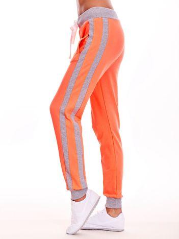 Brzoskwiniowe spodnie dresowe z kieszeniami i lampasami