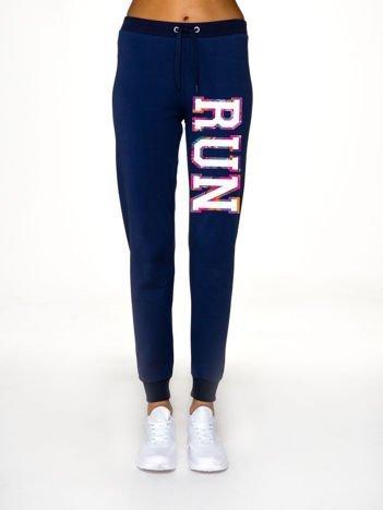 Ciemnoniebieskie spodnie dresowe z napisem RUN na nogawce