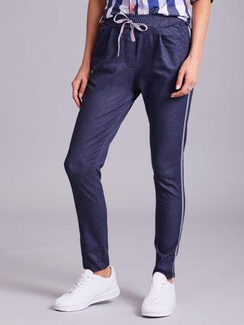 Ciemnoniebieskie spodnie z troczkami i lampasami