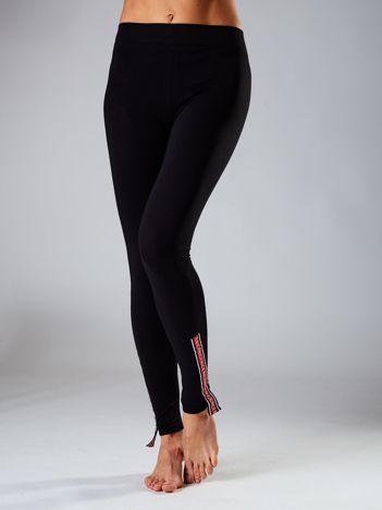 Czarne legginsy z kolorowymi taśmami na nogawkach