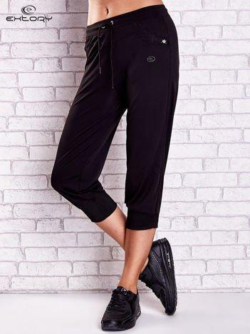 Czarne spodnie capri z dżetami i lampasami