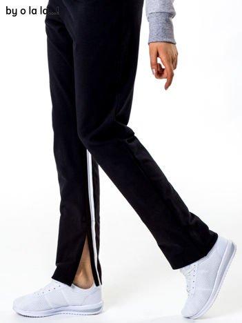 Czarne spodnie dresowe z rozcięciami na nogawkach BY O LA LA
