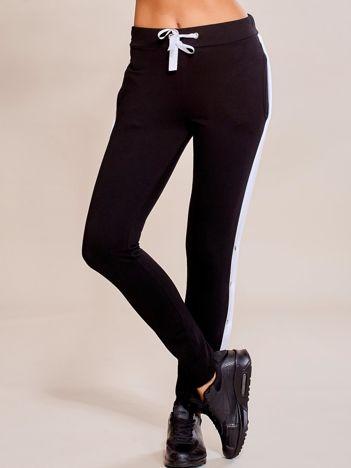 Czarne spodnie dresowe z rozpinanymi nogawkami na napy