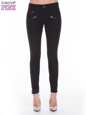 Czarne spodnie jeansowe typu skinny z suwakami na górze i przy nogawkach