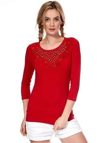 Czerwona bluzka z ozdobnym dekoltem i perełkami