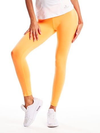 Długie pomarańczowe legginsy fitness o średniej grubości