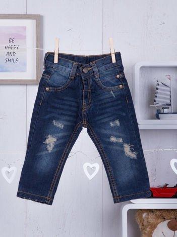 Granatowe jeansy niemowlęce z modnymi przetarciami dla chłopca