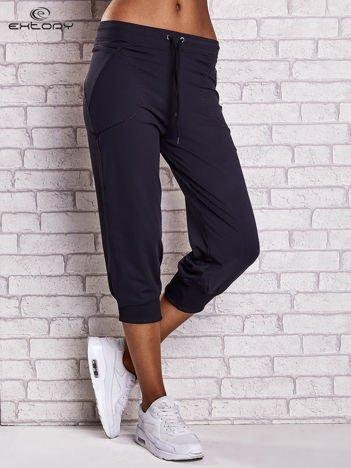 Granatowe spodnie damskie capri z kieszonką i haftem