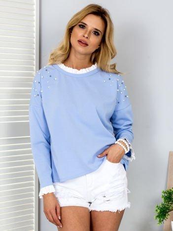 Jasnoniebieska bluzka z perełkami i kontrastowym wykończeniem
