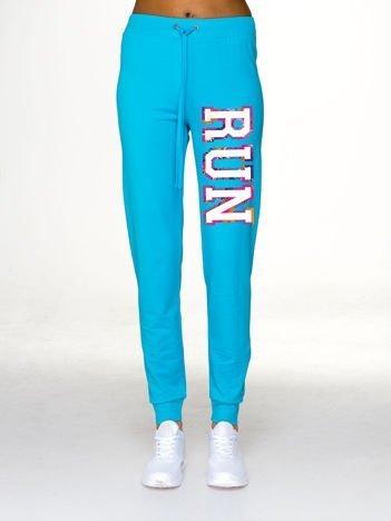 Jasnoniebieskie spodnie dresowe z napisem RUN