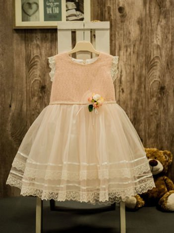 Jasnoróżowa elegancka sukienka dziewczęca z ozdobną różyczką