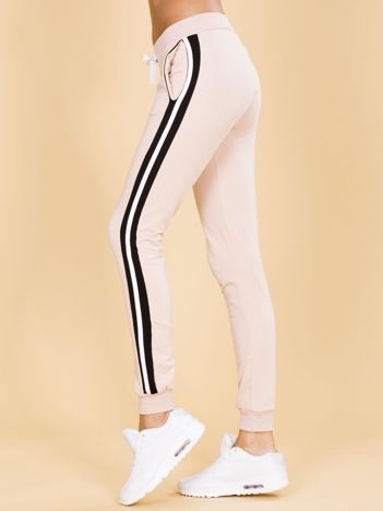 Jasnoróżowe damskie spodnie dresowe z lampasami