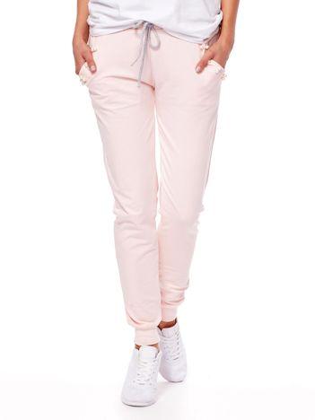 Jasnoróżowe spodnie dresowe z troczkami i perełkami