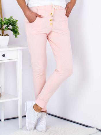 Jasnoróżowe spodnie dresowe ze złotymi guzikami