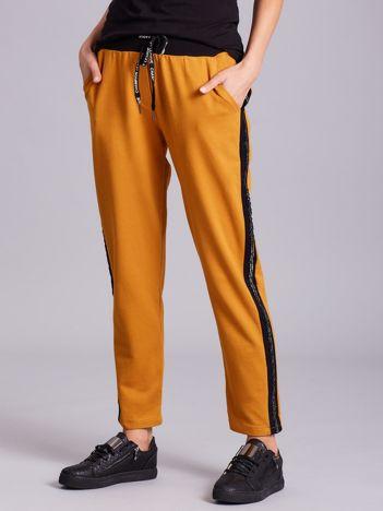 Musztardowe spodnie z lampasami