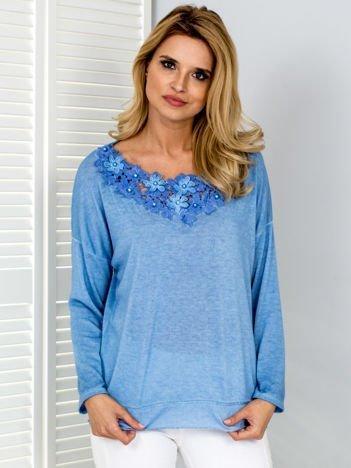 Niebieska bluzka z kwiatową aplikacją