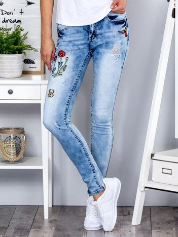 Niebieskie jeansy rurki z naszywkami
