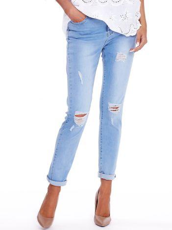 Niebieskie jeansy z przedarciami na kolanach