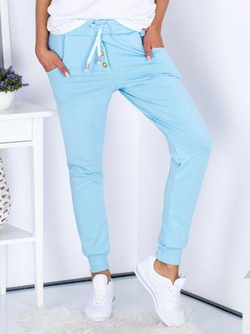 Niebieskie spodnie dresowe ze złotymi guzikami