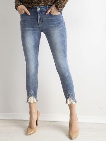 Niebieskie spodnie jeansowe z koronką