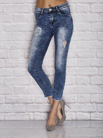 Niebieskie spodnie jeansowe z postrzępioną nogawką