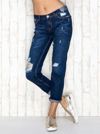 Niebieskie spodnie jeansowe z przetarciami i dziurami