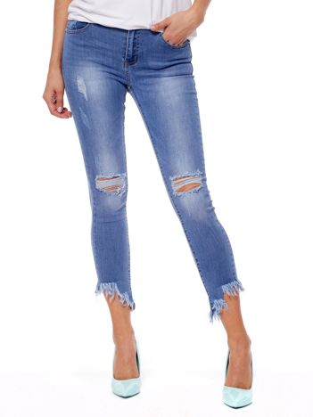 Niebieskie spodnie jeansowe z wystrzępionymi nogawkami i dziurami