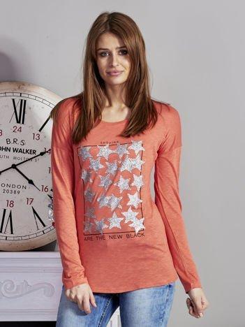 Pomarańczowa bluzka z nadrukiem cekinowych gwiazd