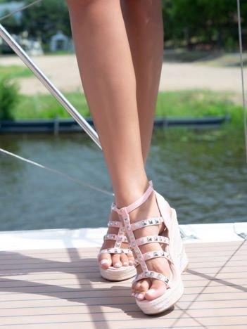 Różowe sandały na koturnach z ozdobnie plecionymi paskami oraz ćwiekami