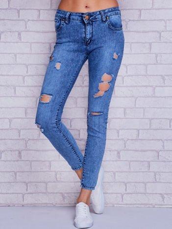 Spodnie jeansowe rurki z dziurami i dekatyzacją niebieski