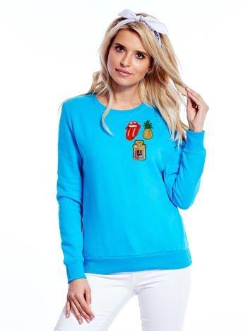 Turkusowa bluza damska z ozdobnymi naszywkami